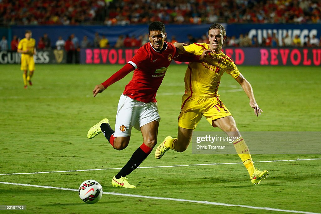 Chris Smalling #12 of Manchester United is challenged by (R) Jordan Henderson #14 of Liverpool in the Guinness International Champions Cup 2014 Final at Sun Life Stadium on August 4, 2014 in Miami Gardens, Florida.