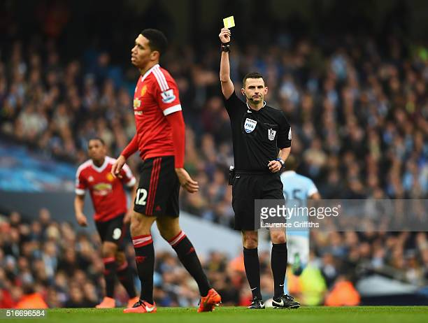 Chris Smalling of Manchester United is shown a yellow card by referee Michael Oliver during the Barclays Premier League match between Manchester City...