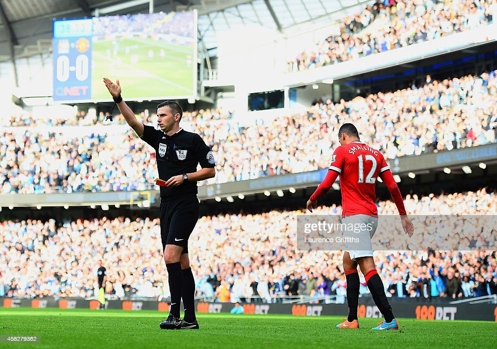 <a gi-track='captionPersonalityLinkClicked' href=/galleries/search?phrase=Chris+Smalling&family=editorial&specificpeople=5964313 ng-click='$event.stopPropagation()'>Chris Smalling</a> of Manchester United leaves the field after receiving a red card by Referee <a gi-track='captionPersonalityLinkClicked' href=/galleries/search?phrase=Michael+Oliver+-+Soccer+Referee&family=editorial&specificpeople=14095035 ng-click='$event.stopPropagation()'>Michael Oliver</a> during the Barclays Premier League match between Manchester City and Manchester United at Etihad Stadium on November 2, 2014 in Manchester, England.