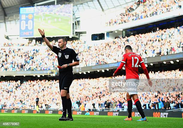 Chris Smalling of Manchester United leaves the field after receiving a red card by Referee Michael Oliver during the Barclays Premier League match...