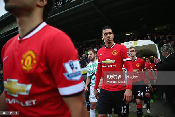 Chris Smalling of Manchester United looks towards the travelling support as the teams enter the field of play during the FA Cup Third Round match...