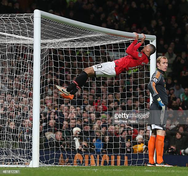 Chris Smalling of Manchester United swings on the crossbar after missing a chance during the Barclays Premier League match between Manchester United...