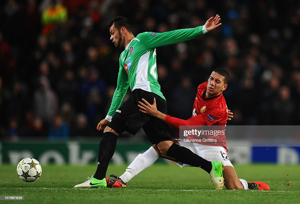 Chris Smalling of Manchester United tangles with Luis Alberto of CFR 1907 Cluj during the UEFA Champions League Group H match between Manchester United and CFR 1907 Cluj at Old Trafford on December 5, 2012 in Manchester, England.