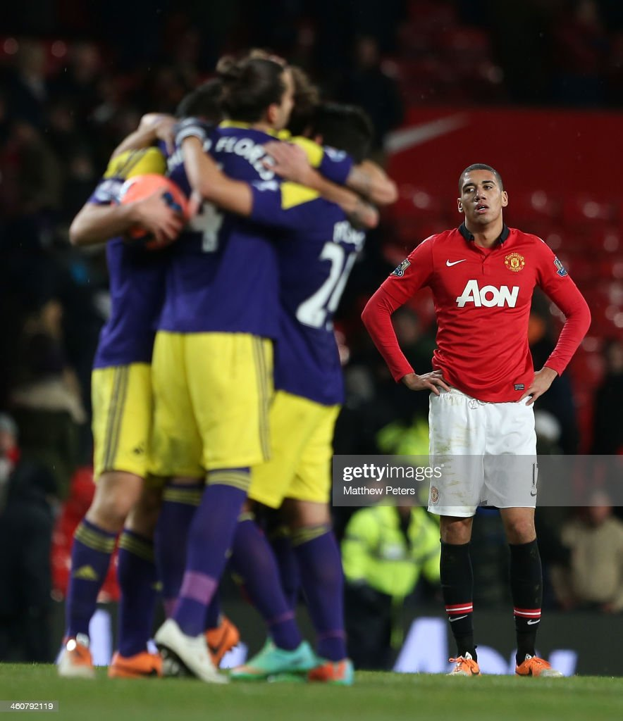 Chris Smalling of Manchester United watches Chico Flores and Alejandro Pozuelo of Swansea City celebrate after their second goal during the FA Cup Third Round match between Manchester United and Swansea City at Old Trafford on January 5, 2014 in Manchester, England.