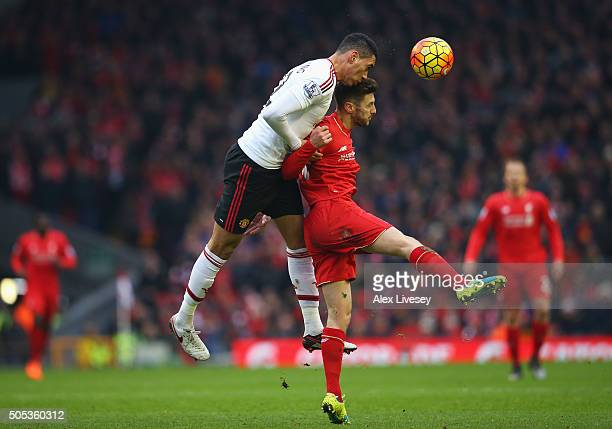 Chris Smalling of Manchester United wins a header from Adam Lallana of Liverpool during the Barclays Premier League match between Liverpool and...