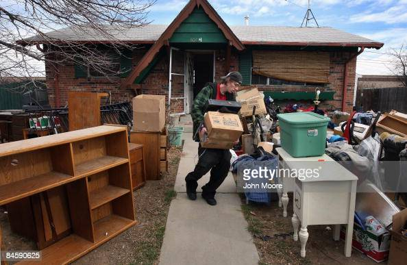 Chris Smith carries out his family's belongings during an official eviction from his foreclosed house on February 2 2009 in Adams County Colorado The...