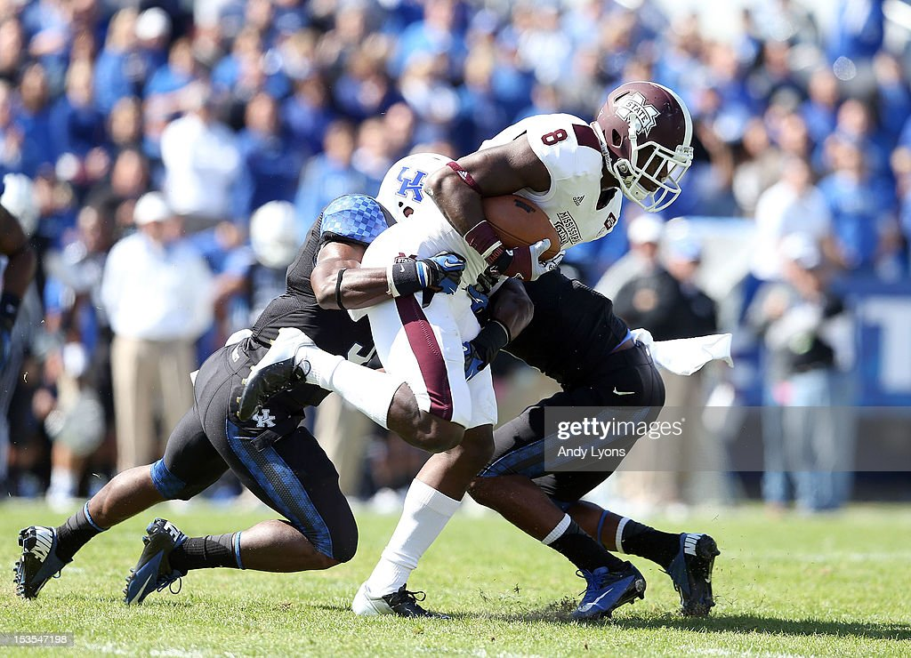 Chris Smith #8 of the Mississippi State Bulldogs runs with the ball while defended by Mikie Benton #31 and Martavius Neloms #1 of the Kentucky Wildcats during the SEC game at Commonwealth Stadium on October 6, 2012 in Lexington, Kentucky. (Photo by Andy Lyons/Getty Images);