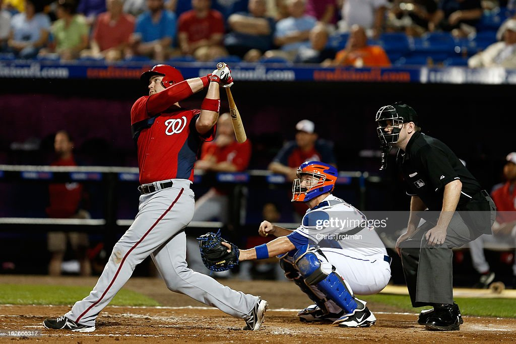 <a gi-track='captionPersonalityLinkClicked' href=/galleries/search?phrase=Chris+Snyder&family=editorial&specificpeople=201238 ng-click='$event.stopPropagation()'>Chris Snyder</a> #7 of the Washington Nationals at swings as <a gi-track='captionPersonalityLinkClicked' href=/galleries/search?phrase=John+Buck&family=editorial&specificpeople=213730 ng-click='$event.stopPropagation()'>John Buck</a> #44 of the New York Mets lookns on at Tradition Field on February 25, 2013 in Port St. Lucie, Florida.