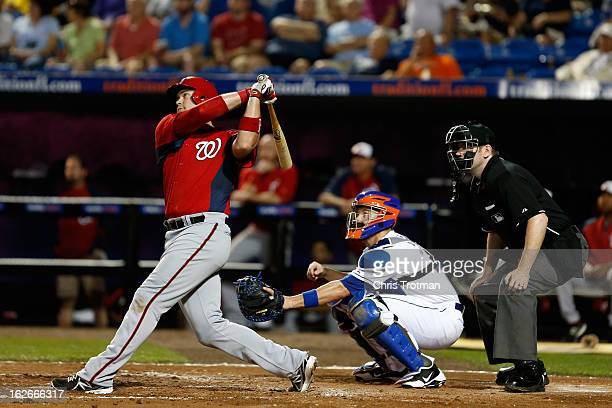 Chris Snyder of the Washington Nationals at swings as John Buck of the New York Mets lookns on at Tradition Field on February 25 2013 in Port St...