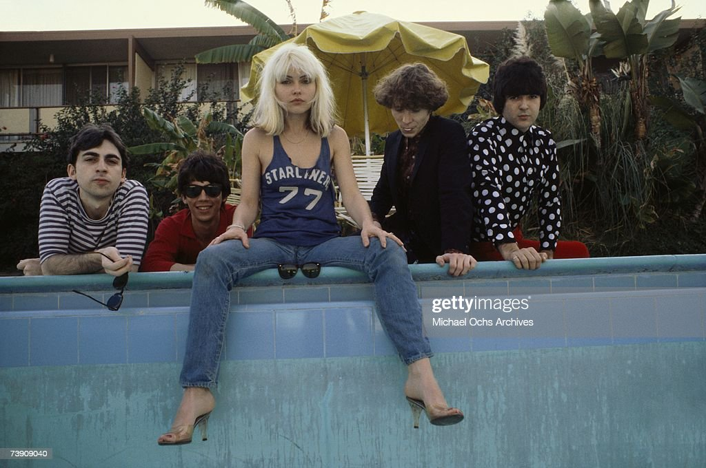 Chris Stein (in striped shirt), Jimmy Destri (in gray shirt with sunglasses), Debbie Harry (in Starliner 77 t-shirt), Gary Valentine (in black suit) and Clem Burke (in polka dot shirt) of the rock and roll band 'Blondie' pose for a portrait session at the Bel Air Sand Hotel in 1977 in Los Angeles, California.