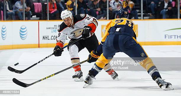 Chris Stewart of the Anaheim Ducks dumps the puck in the zone against Paul Gaustad of the Nashville Predators during an NHL game at Bridgestone Arena...