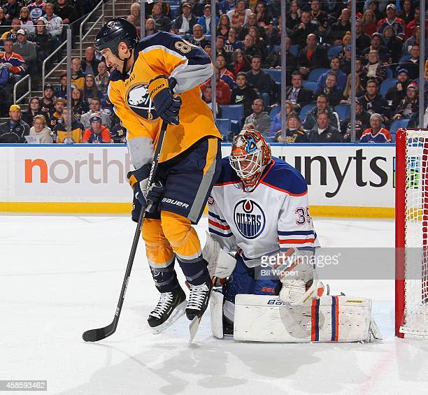 Chris Stewart of the Buffalo Sabres jumps to avoid a shot while screening goaltended Victor Fasth of the Edmonton Oilers on November 7 2014 at the...