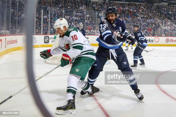 Chris Stewart of the Minnesota Wild and Dustin Byfuglien of the Winnipeg Jets battle for the puck along the boards during first period action at the...