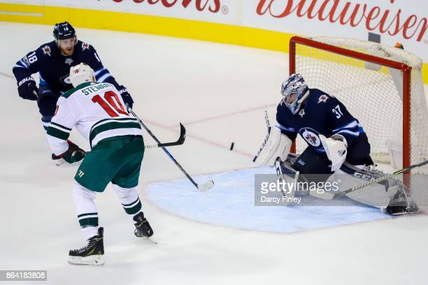 Chris Stewart of the Minnesota Wild backhands the puck past goaltender Connor Hellebuyck of the Winnipeg Jets for a first period goal at the Bell MTS...