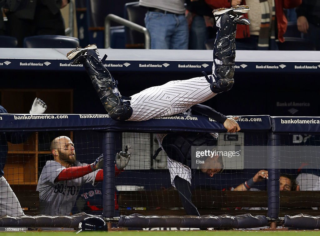Chris Stewart #19 of the New York Yankees catches a foul ball by Shane Victorino of the Red Sox for the out as <a gi-track='captionPersonalityLinkClicked' href=/galleries/search?phrase=Dustin+Pedroia&family=editorial&specificpeople=836339 ng-click='$event.stopPropagation()'>Dustin Pedroia</a> #15 of the Boston Red Sox tries to stop Stewart as he falls into the dugout on April 3, 2013 at Yankee Stadium in the Bronx borough of New York City.