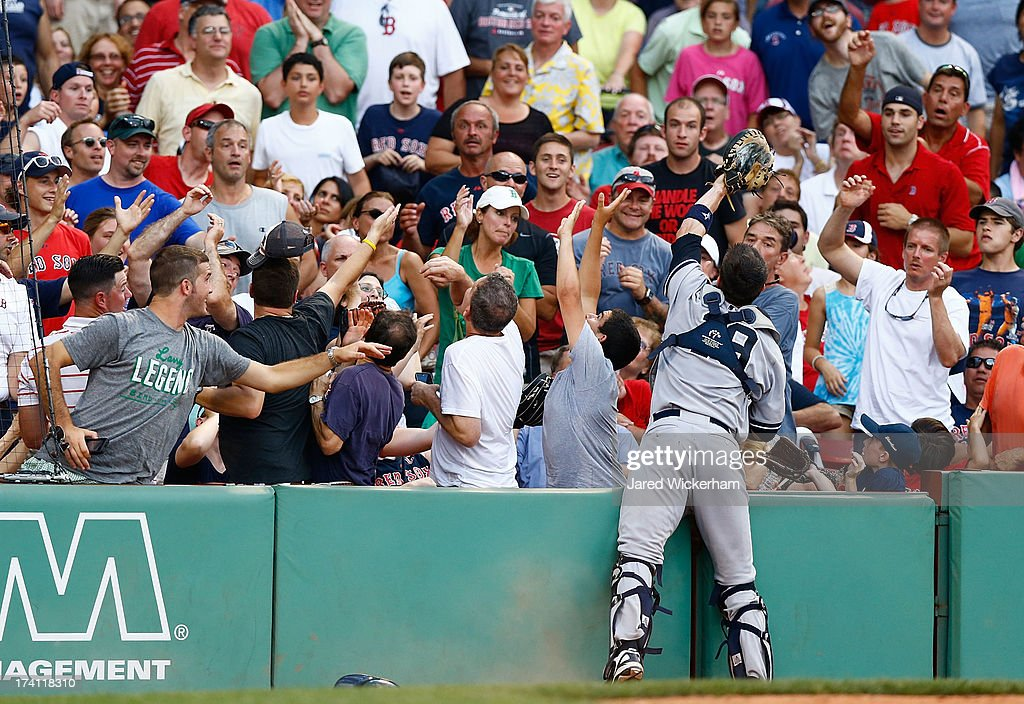 Chris Stewart #19 of the New York Yankees catches a foul ball in the stands in the 8th inning against the Boston Red Sox during the game on July 20, 2013 at Fenway Park in Boston, Massachusetts.