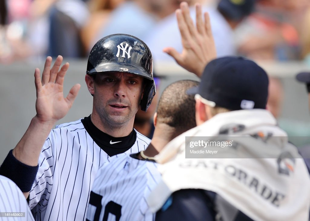 Chris Stewart #19 of the New York Yankees celebrates with teammates after scoring a run in the third inning against the San Francisco Giants during interleague play on September 21, 2013 at Yankee Stadium in the Bronx borough of New York City. The Yankees defeat the Giants 6-0.