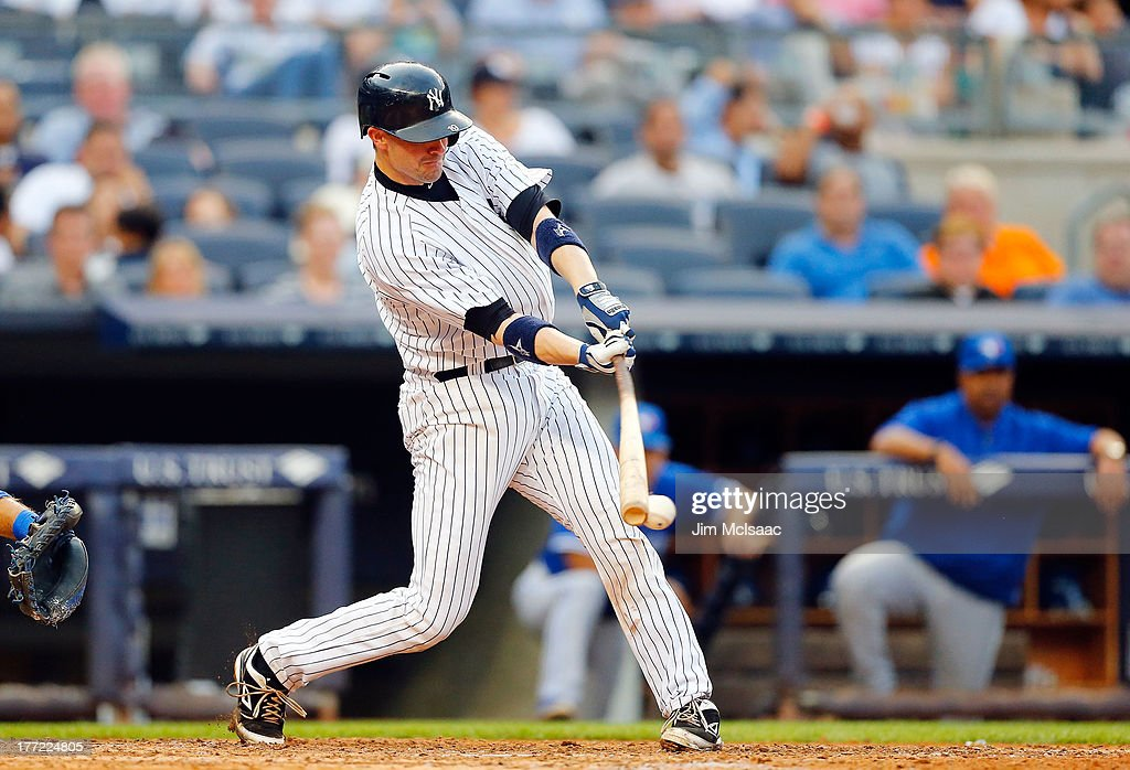 Chris Stewart #19 of the New York Yankees connects on a sixth inning run scoring ground out against the Toronto Blue Jays at Yankee Stadium on August 22, 2013 in the Bronx borough of New York City.