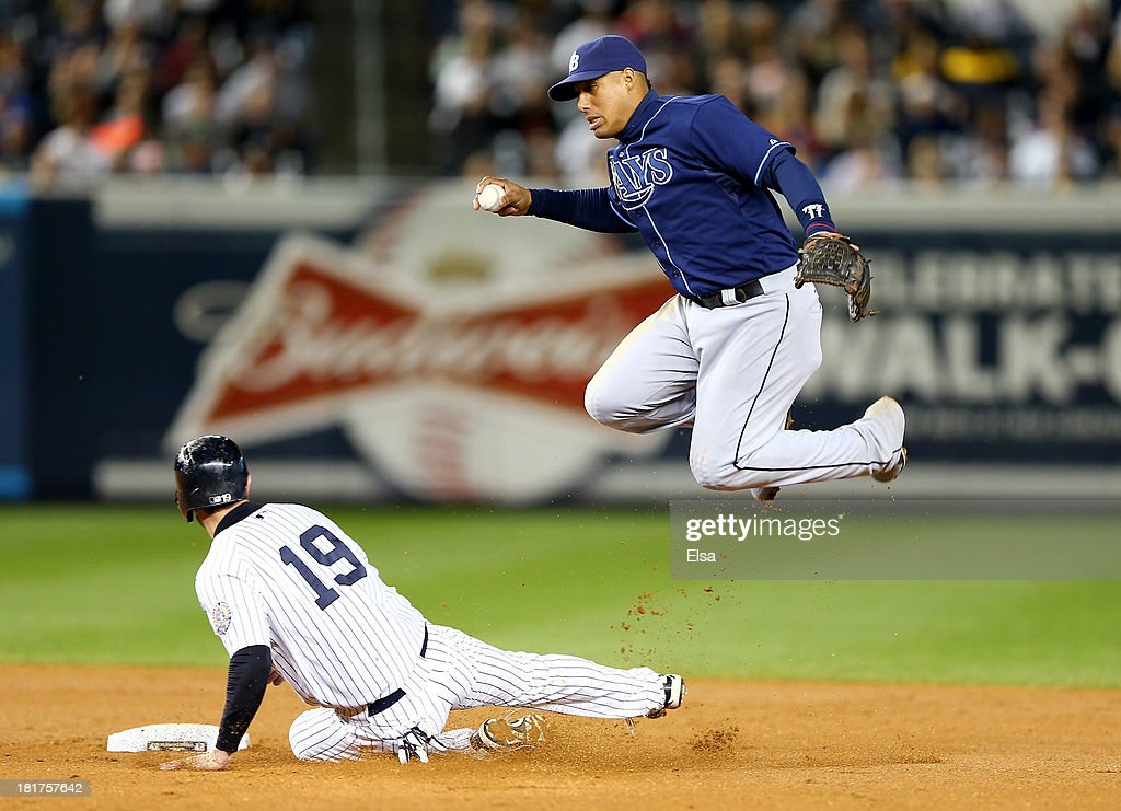 Chris Stewart #19 of the New York Yankees is out at second but Yunel Escobar #11 of the Tampa Bay Rays is unable to turn the double play in the fourth inning on September 24, 2013 at Yankee Stadium in the Bronx borough of New York City.
