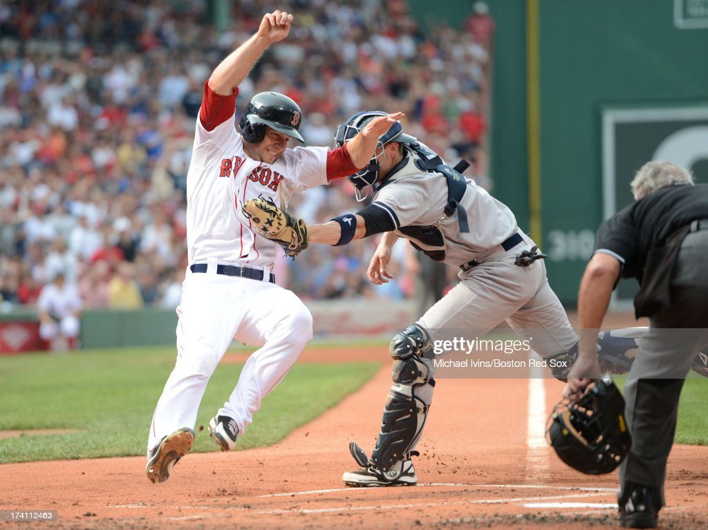 Chris Stewart #19 of the New York Yankees tags out <a gi-track='captionPersonalityLinkClicked' href=/galleries/search?phrase=Daniel+Nava&family=editorial&specificpeople=670454 ng-click='$event.stopPropagation()'>Daniel Nava</a> #29 of the Boston Red Sox in the first inning on July 20, 2013 at Fenway Park in Boston, Massachusetts.