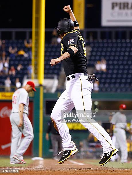 Chris Stewart of the Pittsburgh Pirates celebrates after sliding safely into home plate to score the gamewinning run in the 13th inning against the...