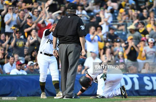 Chris Stewart of the Pittsburgh Pirates grabs his knee after sliding into third base with a two run triple in the seventh inning during the game...