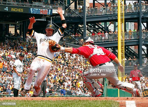 Chris Stewart of the Pittsburgh Pirates scores against Wilson Ramos of the Washington Nationals on an RBI single in the third inning during the game...