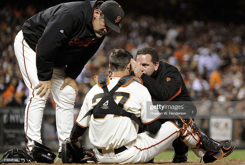 Chris Stewart #37 of the San Francisco Giants is checked out by head trainer Dave Groescher and manager <a gi-track='captionPersonalityLinkClicked' href=/galleries/search?phrase=Bruce+Bochy&family=editorial&specificpeople=220291 ng-click='$event.stopPropagation()'>Bruce Bochy</a> #15 after Stewart was hit in the head by the back swing of Aaron Miles of the Los Angeles Dodgers in the sixth inning during an MLB baseball game at AT&T Park July 18, 2011 in San Francisco, California.