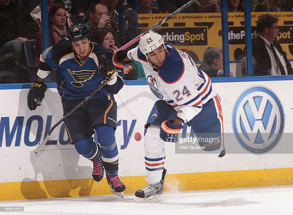 Chris Stewart #25 of the St. Louis Blues races Theo Peckham #24 of the Edmonton Oilers up the ice in an NHL game on March 1, 2013 at Scottrade Center in St. Louis, Missouri.