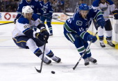 Chris Stewart of the St Louis Blues tries to check Jordan Schroeder of the Vancouver Canucks during the second period in NHL action on March 19 2013...