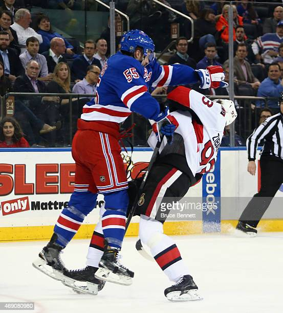 Chris Summers of the New York Rangers hits Mika Zibanejad of the Ottawa Senators during the first period at Madison Square Garden on April 9 2015 in...