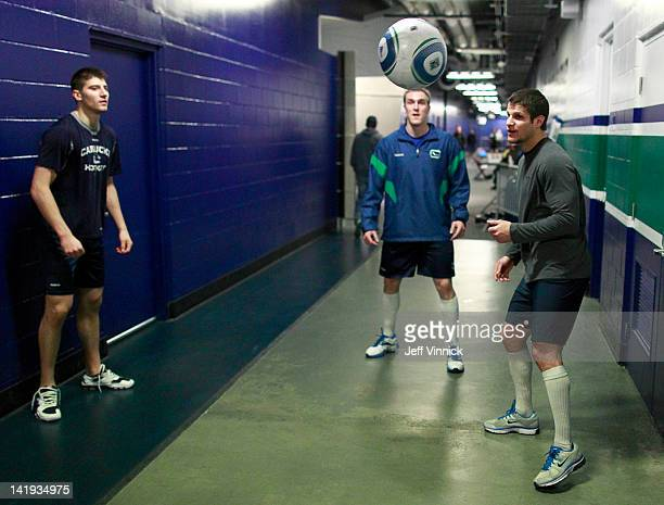 Chris Tanev Dale Weise and Kevin Bieksa of the Vancouver Canucks play soccer as they warm up before the start of their NHL game against the Los...
