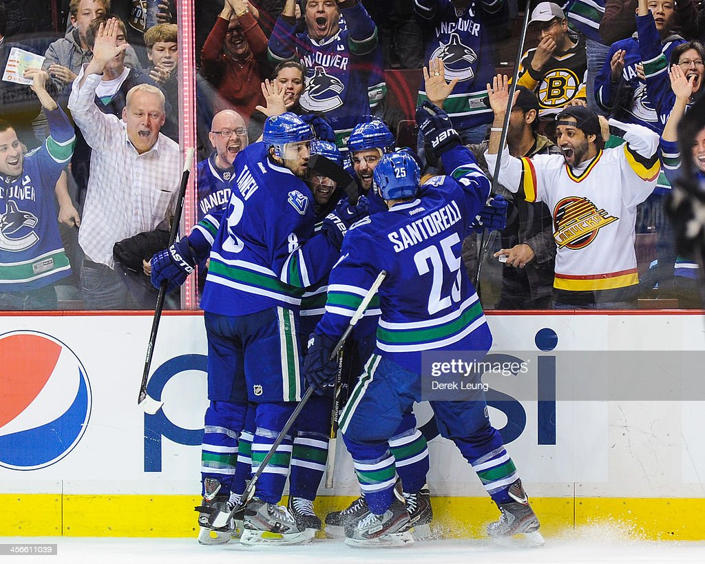 Chris Tanev #8, <a gi-track='captionPersonalityLinkClicked' href=/galleries/search?phrase=Dan+Hamhuis&family=editorial&specificpeople=204213 ng-click='$event.stopPropagation()'>Dan Hamhuis</a> #2, and Chris Higgins #20 and <a gi-track='captionPersonalityLinkClicked' href=/galleries/search?phrase=Mike+Santorelli&family=editorial&specificpeople=4517042 ng-click='$event.stopPropagation()'>Mike Santorelli</a> #25 of the Vancouver Canucks celebrate after Chris Higgins scored the team's third goal against the Boston Bruins during an NHL game at Rogers Arena on December 14, 2013 in Vancouver, British Columbia, Canada.