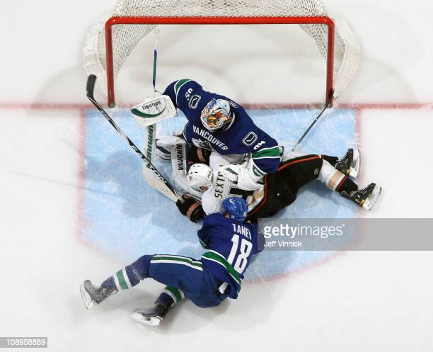 Chris Tanev of the Vancouver Canucks and Dan Sexton of the Anaheim Ducks crash into Cory Schneider of the Vancouver Canucks during their game at...