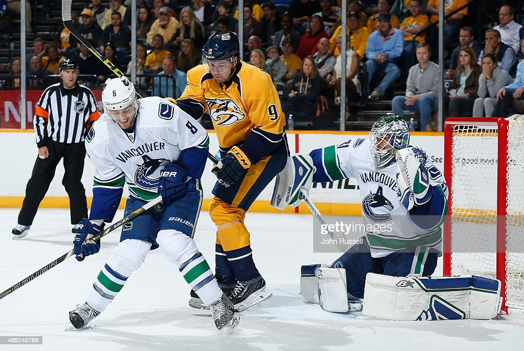 Chris Tanev #8 of the Vancouver Canucks blocks a shot against Filip Forsberg #9 of the Nashville Predators as they battle in front of Canucks goalie Eddie Lack #31 during an NHL game at Bridgestone Arena on March 31, 2015 in Nashville, Tennessee.