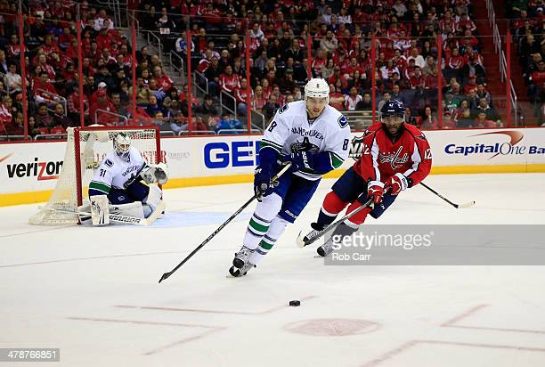 Chris Tanev of the Vancouver Canucks moves the puck in front of Joel Ward of the Washington Capitals during the third period of the Capitals 43 win...