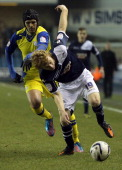 Chris Taylor of Millwall is tackled by Miguel Llera of Sheffield Wednesday during the npower Championship match between Millwall and Sheffield...