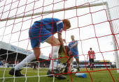 Chris Taylor of Oldham tries to get the ball from goalkeeper Stuart Nelson of Brentford during the CocaCola League One match between Brentford and...