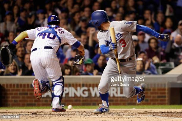 Chris Taylor of the Los Angeles Dodgers attempts to reach first base as Willson Contreras of the Chicago Cubs chases after a dropped third strike in...