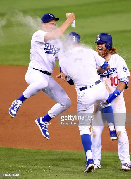 Chris Taylor of the Los Angeles Dodgers celebrates his game winning hit with Justin Turner and Enrique Hernandez for a 54 win over the Arizona...