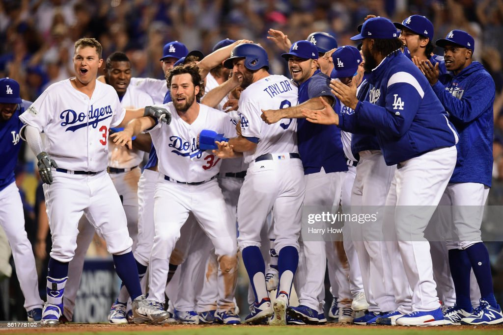 Chris Taylor #3 of the Los Angeles Dodgers celebrates with teammates as he scores a run after Justin Turner #10 (not pictured) hit a three-run walk-off home run in the ninth inning to defeat the Chicago Cubs 4-1 in game two of the National League Championship Series at Dodger Stadium on October 15, 2017 in Los Angeles, California.