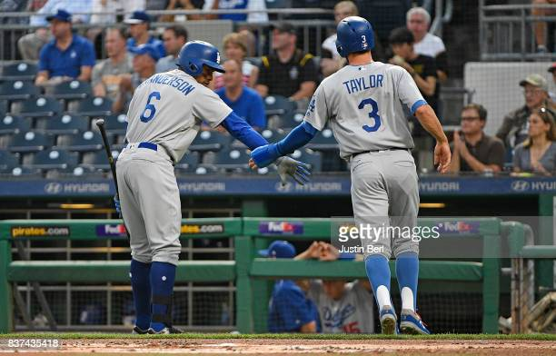 Chris Taylor of the Los Angeles Dodgers is greeted by Curtis Granderson after coming around to score on a RBI groundout by Justin Turner in the first...