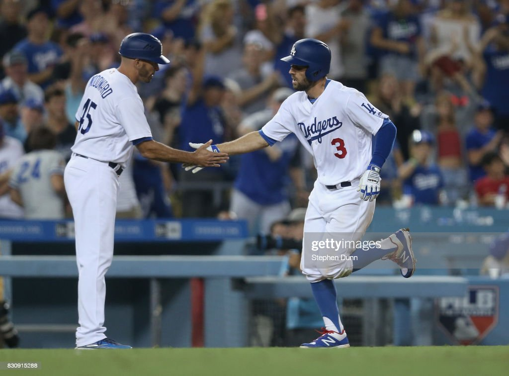 Chris Taylor #3 of the Los Angeles Dodgers is greeted by third base Chris Woodward #45 as he rounds third after hitting a solo home run in the eighth inning against the San Diego Padres at Dodger Stadium on August 12, 2017 in Los Angeles, California.