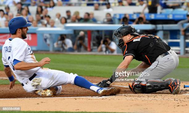 Chris Taylor of the Los Angeles Dodgers is tagged out at home by JT Realmuto of the Miami Marlins in the first inning of the game at Dodger Stadium...