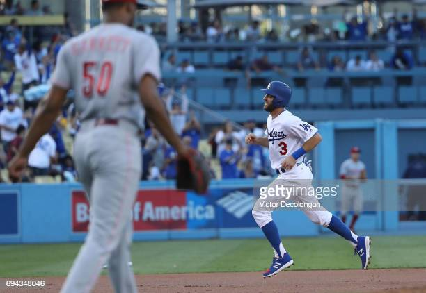 Chris Taylor of the Los Angeles Dodgers jogs to third base en route to home on a homerun by teammate Justin Turner as pitcher Amir Garrett of the...