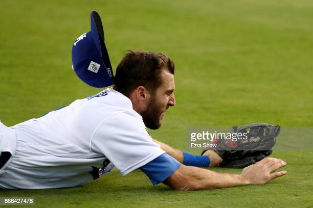 Chris Taylor of the Los Angeles Dodgers loses his hat as he attempts to catch a RBI single hit by Alex Bregman of the Houston Astros during the third...