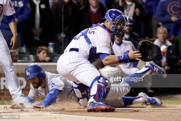 Chris Taylor of the Los Angeles Dodgers slides into home plate to score a run past Willson Contreras of the Chicago Cubs in the first inning during...