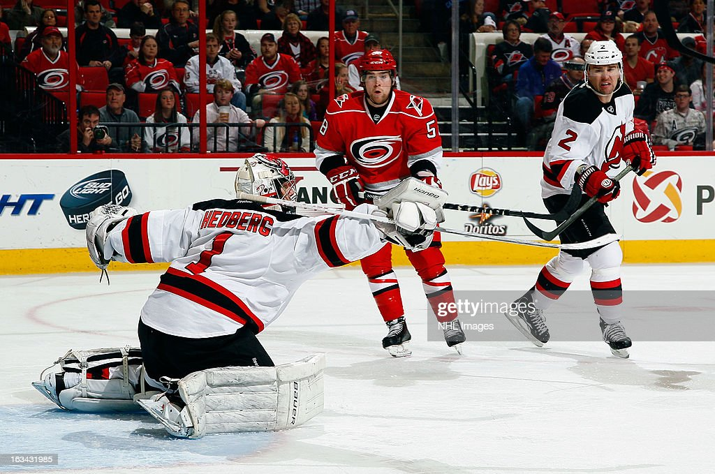 Chris Terry #58 of the Carolina Hurricanes and <a gi-track='captionPersonalityLinkClicked' href=/galleries/search?phrase=Marek+Zidlicky&family=editorial&specificpeople=203291 ng-click='$event.stopPropagation()'>Marek Zidlicky</a> #2 of the New Jersey Devils watch a puck deflect off the blocker of <a gi-track='captionPersonalityLinkClicked' href=/galleries/search?phrase=Johan+Hedberg&family=editorial&specificpeople=202078 ng-click='$event.stopPropagation()'>Johan Hedberg</a> #1 during an NHL game on March 9, 2013 at PNC Arena in Raleigh, North Carolina.