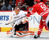 Chris Terry of the Carolina Hurricanes attempts to deflect a shot on goal as Viktor Fasth of the Anaheim Ducks prepares to make a save during their...