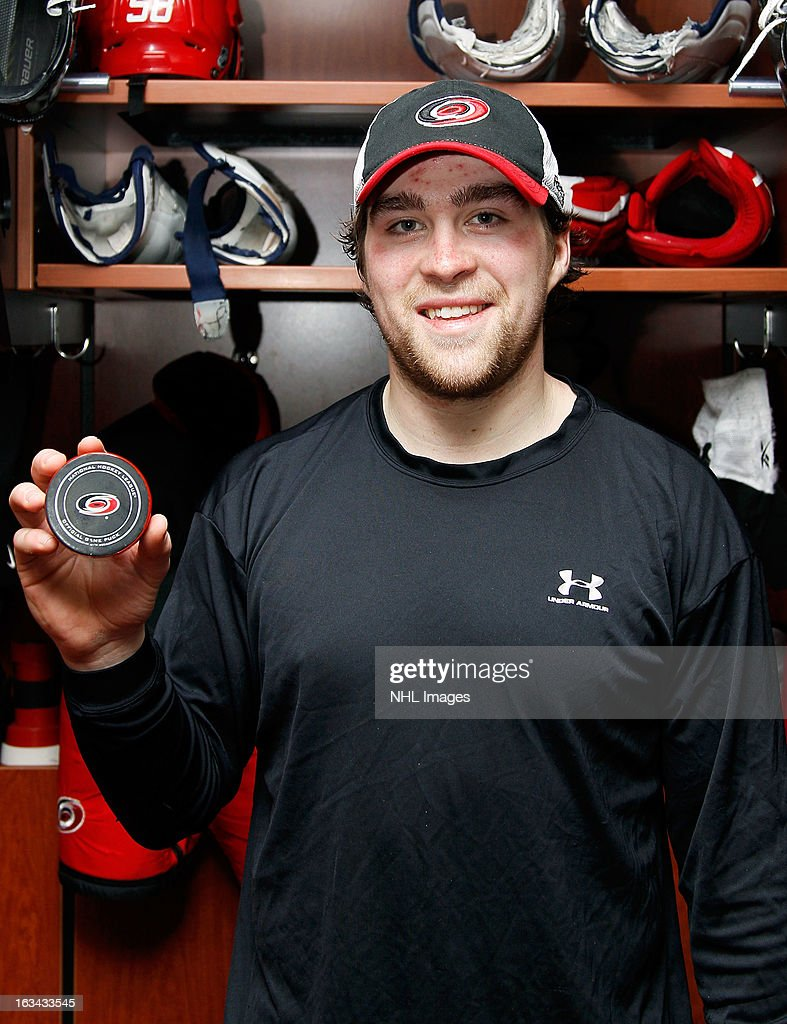 Chris Terry #58 of the Carolina Hurricanes is pictured following the team's 6-3 victory over the New Jersey Devils with the puck from his first NHL goal, what would be the game-winning goal, in his first NHL game on March 9, 2013 at PNC Arena in Raleigh, North Carolina.